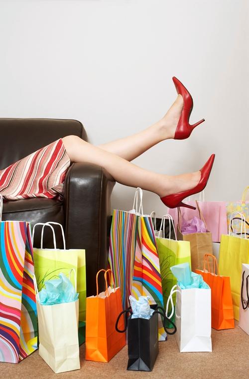 Frauenbeine ragen von einer Couch. Neben der Couch befinden sich ganz viele Einkaufstüten.