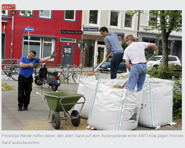 Tatkräftige Helfer: Drei männliche Helfer stehen mit Schaufeln, Schubkarre und Sandsäcken auf dem Außengelände einer AWO-Kita und tauschen alten Sand gegen neuen aus.