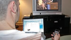 Mann schaut TV und surft auf Tablet