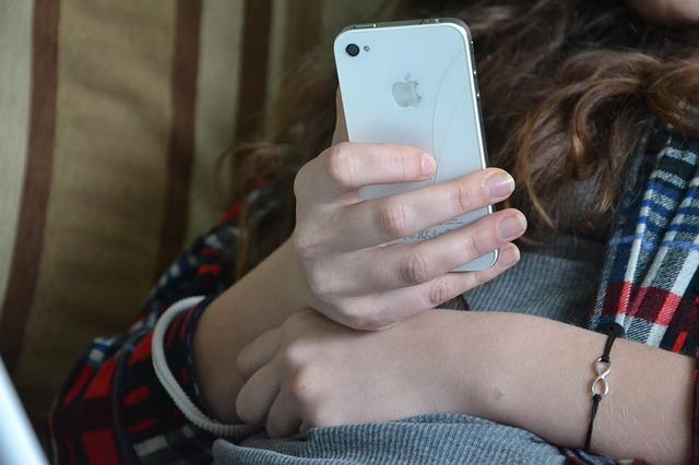 mit smartphone auf dem sofa