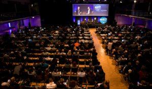 Eine volle Halle mit Menschen, die einem Speaker zuhören auf der SEOkomm 2017.