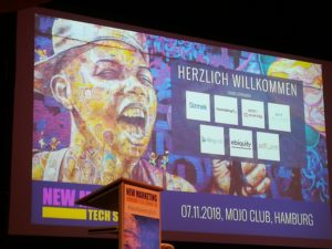 Foto der Leinwand und des Rednerpults auf der New Marteing Tech Summit 2018 im Mojo Club in Hamburg.