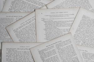 Rausgerissene Buchseiten mit unterschiedlichen Seitenzahlen auf einem Stapel.